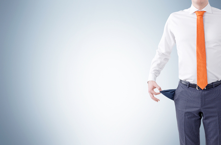 empty pocket: Unemployment concept with businessman showing empty pocket on light grey background. Mock up