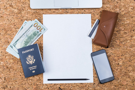 cork sheet: Top view of cork table with blank paper sheet, smartphone, eyeglass case, american passport and dollars. Traveling concept. Mock up Stock Photo