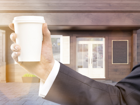 toned: Hand holding blank coffee cup on cafe exterior background. Toned image. Mock up, 3D Rendering