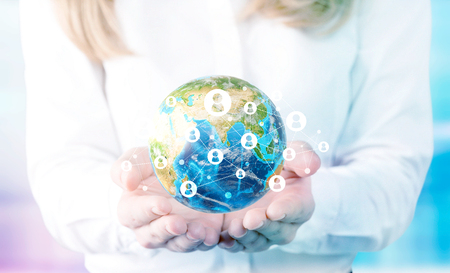 hands holding globe: Businesswoman hands holding globe with social networking system on blue background. Elements of this image furnished by NASA Stock Photo