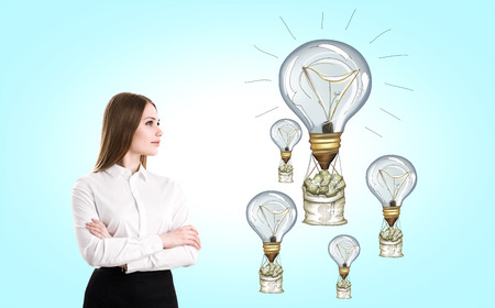 nags: Success concept with businesswoman looking at lightbulb airballoons with money nags