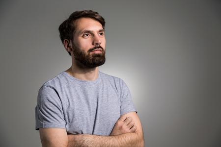 Jonge man met baard en gekruiste armen op lichtgrijze achtergrond