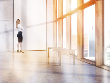 toned: Thoughtful businesswoman standing in interior with blank white banner and bench. Toned image. 3D Rendering Stock Photo