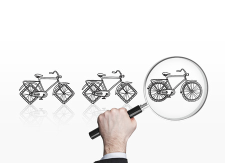 nonpolluting: Businessman looking at bicycle sketches through magnifying glass trying to choose the most suitable one. Commuting concept Stock Photo