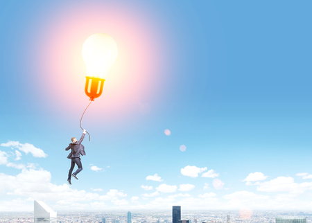 flying man: Idea concept with man flying on illuminated lightbulb balloon over New York city Stock Photo