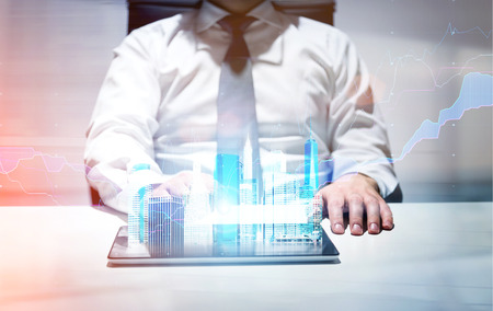 holograph: Businessman in office using tablet with New York city gologram and business chart Stock Photo
