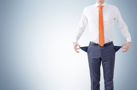 penniless: Unemployment concept with businessman showing empty pockets on grey background. Mock up