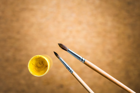 paint container: Two brushes and yellow gouache paint container on blurry brown background Stock Photo