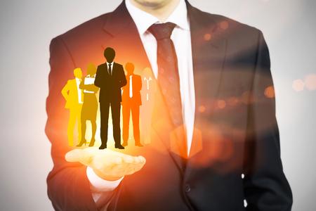 Humanressourcen-Konzept mit Mann im Anzug leuchtend orange Geschäftsleute Silhouetten halten