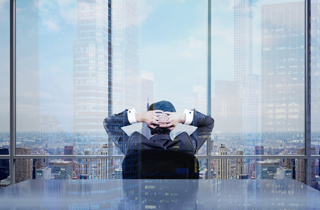 admiring: Back view of thoughtful  businessman sitting on chair in office admiring New York city view. Double exposure