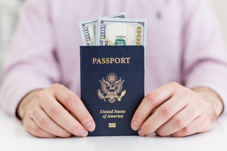 White desktop with american passport and dollars in businessman's hands