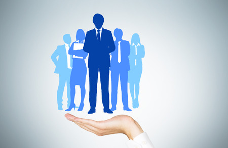 inferior: Human resources concept with mans hand holding businesspeople silhouettes