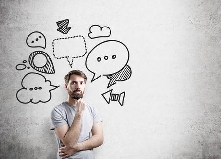 Pensare uomo d'affari con parola e pensiero bolle sul muro di cemento