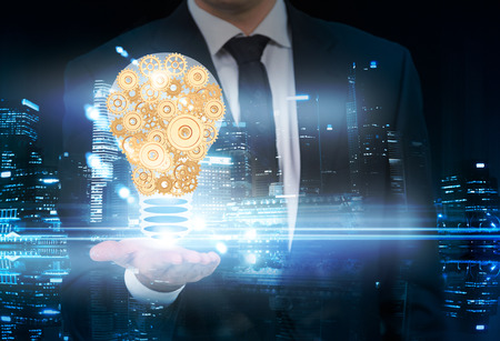 business gears: Idea concept with businessman holding abstract lightbulb made of golden gears on New York city background. Double exposure Stock Photo