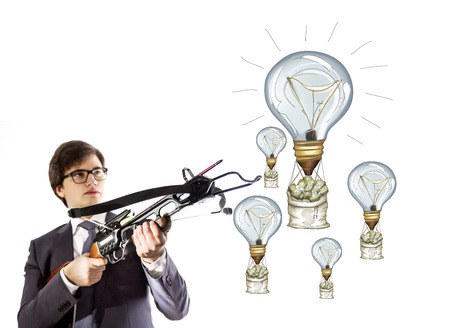 crossbow: Success concept with businessman aiming at lightbulb airballoons and money sacks with crossbow Stock Photo