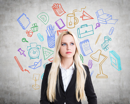 businesswoman standing: Thinking businesswoman standing against concrete wall with colorful office accessories sketch Stock Photo