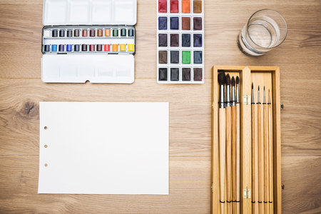 watercolor paper: Top view of wooden table with set of paintbrushes, blank paper sheet, water-color and glass of water. Mock up