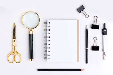 stationery items: Top view of blank spiral notepad, golden scissors, magnifier and other stationery items on white background. Mock up