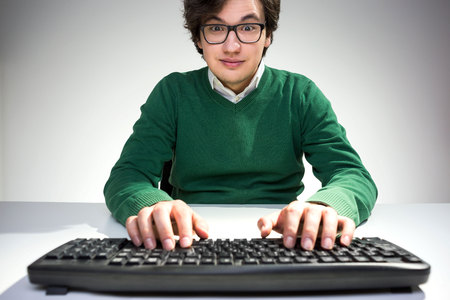 raised eyebrows: Surprised young man with raised eyebrows using computer keyboard on white desktop Stock Photo
