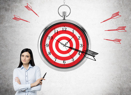 timelines: Time management and targeting concept with abstarct dartboard clock and businesswoman on concrete background