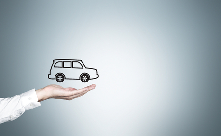 man holding transparent: Businessman hand with car icon on light grey background