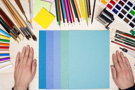 Artists hands next to colorful paper sheets and drawing tools on wooden table. Top view, Mock up