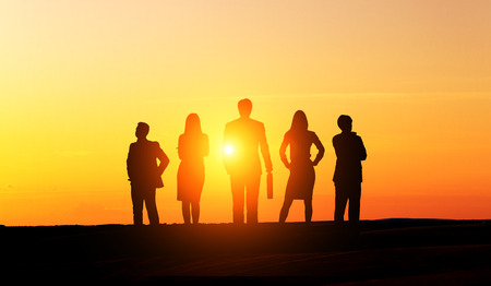 Businesspeople silhouettes at sunset. Concept of teamwork and partnership