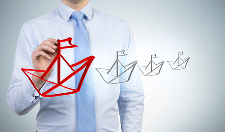 drawing large: Leadership concept with businessman drawing large red paper boat icon on grey background Stock Photo