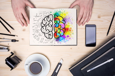 Top view of wooden desktop with coffee cup, stationery items, smart phone and hands holding notepad with creative and analytical brain sides sketch