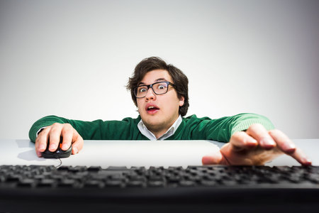 front desk: Crazy young man sitting on floor in front of desk with hand on mouse and trying to reach computer keyboard Stock Photo
