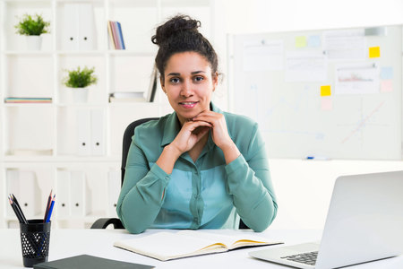 stationery items: Attractive african american woman sitting at office desk with laptop, stationery items, looking at the camera and smiling