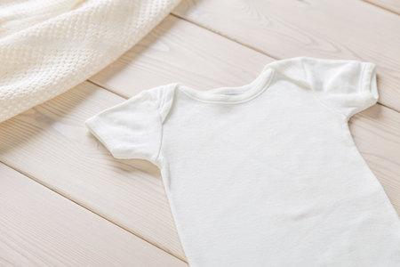 木製デスクトップ上の白い赤ちゃんシャツ。モックアップします。