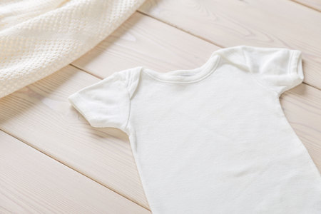 White baby shirt on wooden desktop. Mock up