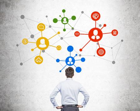 Concetto del sistema di rete sociale con l'uomo d'affari che esamina schizzo variopinto sul muro di cemento