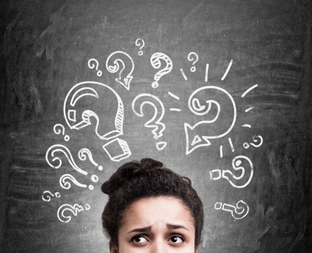 hesitation: Confused african american woman thinking about answers to her questions on chalkboard background Stock Photo