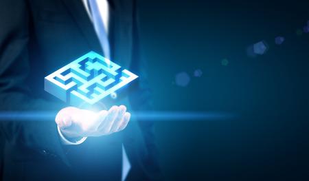 Concept de défi commercial représenté par la main de l'homme d'affaires détenant le labyrinthe illuminé abstrait