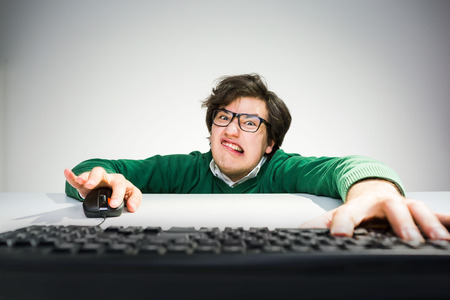 front desk: Funny young man with crazy face sitting on floor in front of desk with hands on mouse and computer keyboard