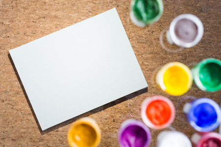 cork sheet: Blank paper sheet and blurry gouache paint jars on cork background. Mock up Stock Photo