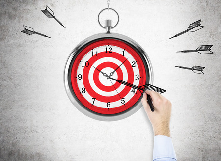 timelines: Time management and targeting concept with businessman hand drawing a dart on abstract dartboard clock on concrete background Stock Photo