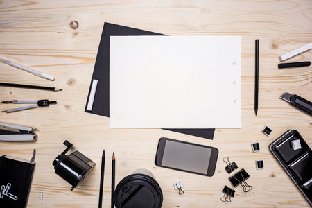 stationery items: Top view of wooden desk with blank paper sheet, smart phone and various stationery items. Mock up Stock Photo