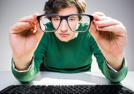 raised eyebrows: Crazy young man with raised eyebrows sitting at desk with computer keyboard and looking at the camera through glasses Stock Photo