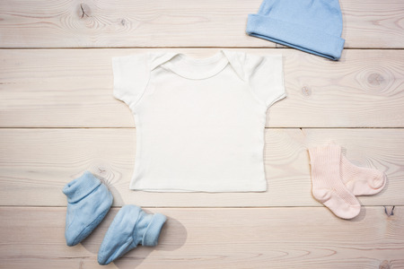 Baby apparel on wooden desktop. Mock up Stock Photo