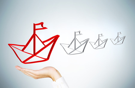 hand holding paper: Leadership concept with businessman hand holding red paper ship icon