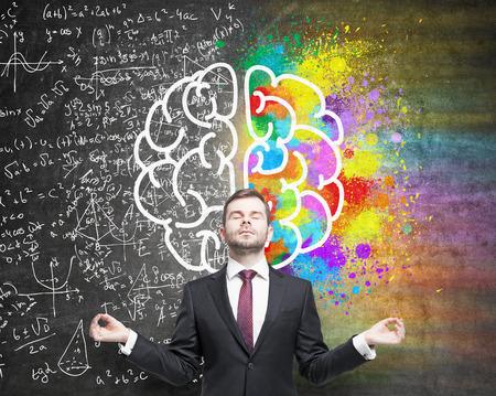 Rechter en linker hemisfeer, creatief en analytisch denken concept met zakenman mediteren tegen schoolbord met schets