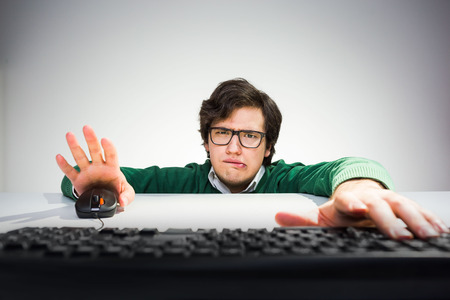 front desk: Crazy young man with funny face sitting on floor in front of desk with hands on mouse and computer keyboard Stock Photo