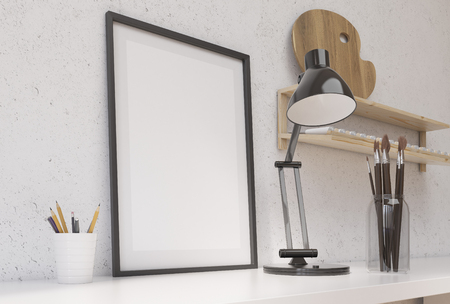 artist's canvas: Side view of white desktop with blank picture frame, brushes, pencils, lamp and wooden shelf with empty paint palette above on concrete wall. Mock up, 3D Rendering