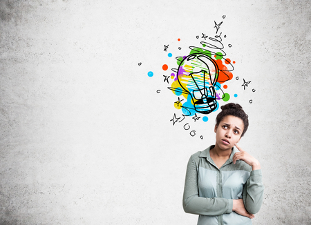 confused face: Creative idea concept with thoughtful african american woman and colorful lightbulb sketch on concrete background Stock Photo