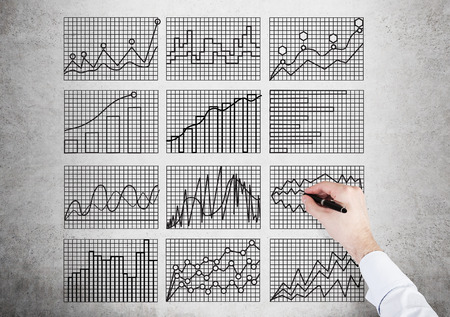 concrete background: Businessman hand drawing business charts on grid. Concrete background Stock Photo