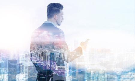 Stylish businessman using smart phone on New York city background. Double exposure Stock Photo