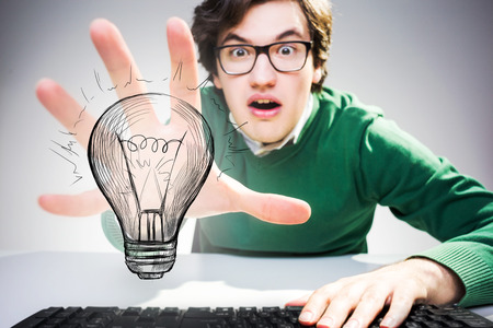 grabbing: Idea concept with astonished young man sitting at desk with keyboard and grabbing abstract lightbulb sketch Stock Photo
